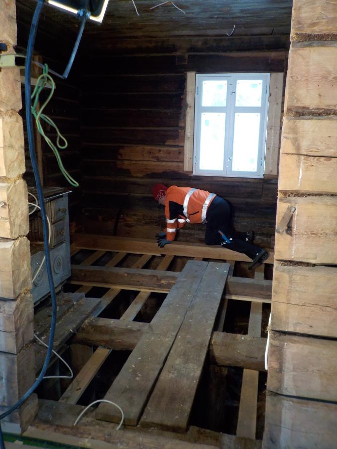 Isäntä konttaa lattiaparrun päällä ja suunnittelee lattian rakennetta.
