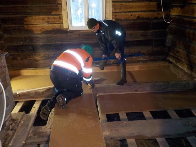 Miehet laittavat keittiön lattiaan tuulensuojalevyjä paikoilleen